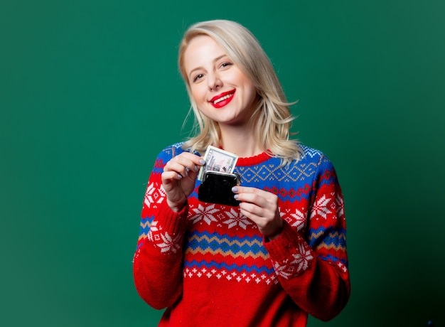 Beautiful woman in christmas sweater holds purse with money