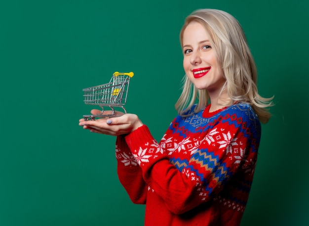Beautiful woman in christmas sweater holds shopping cart