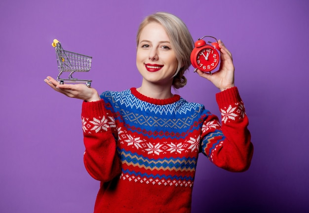 Beautiful woman in christmas sweater with alarm clock and shopping cart