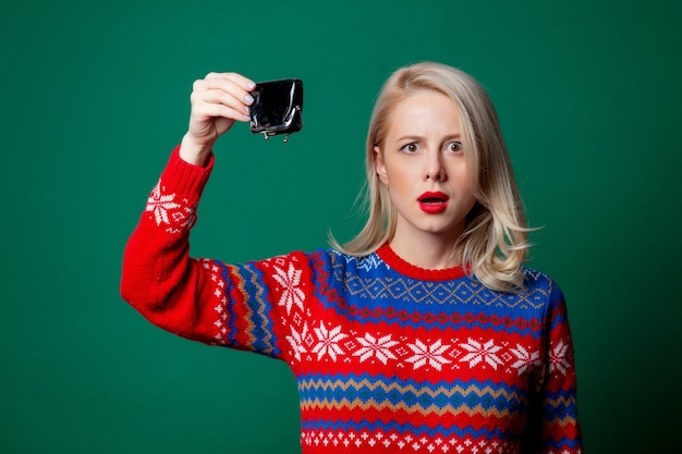 Beautiful woman in christmas sweater with empty purse