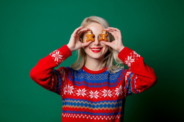 Beautiful woman in christmas sweater with gingerbread man cookies