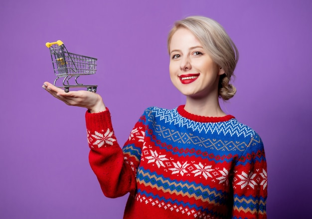 Beautiful woman in christmas sweater with shopping cart