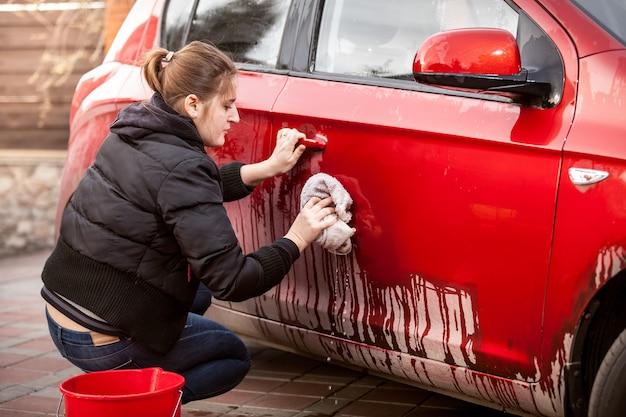 Красивая женщина чистит дверь машины от грязи и грязи