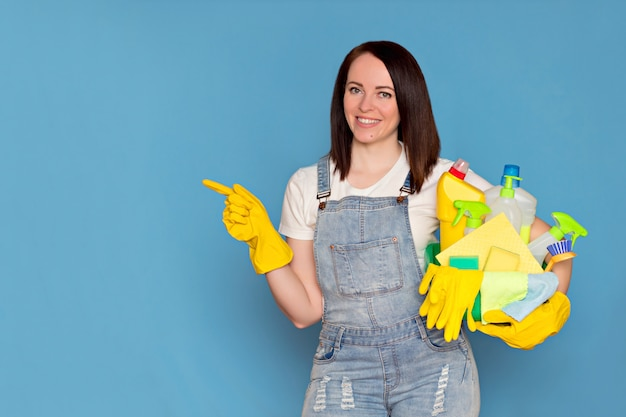 Beautiful woman cleaning lady with a bucket of detergent in rubber gloves
