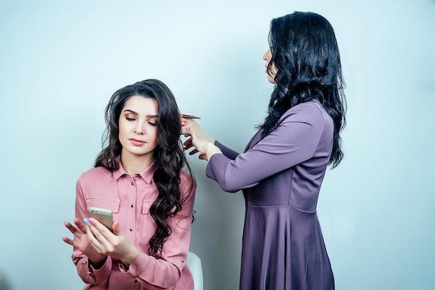 미용실에 앉아 있는 아름다운 여성 클라이언트와 헤어스타일을 하는 스타일리스트 미용사