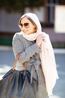 Bella donna in un cappotto in posa sulla strada