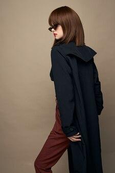 Красивая женщина пальто с поясом яркий макияж смеясь студийный портрет