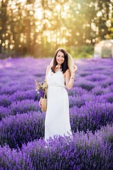 Красивая женщина собирает лаванду. девушка в белом сарафане и шляпе летом на природе