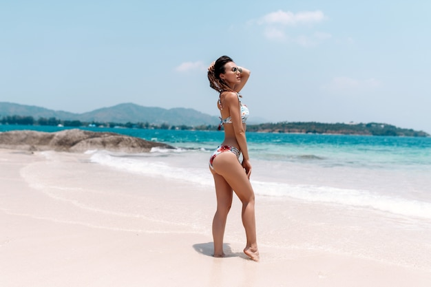 Beautiful woman in colorful swimwear with long hair posing on beach with white sand