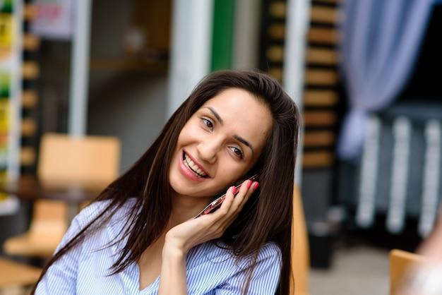 Красивая женщина общается по телефону на улице.