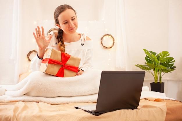 아름다운 여인은 비디오 링크를 통해 온라인으로 크리스마스에 사랑하는 사람들을 축하합니다.