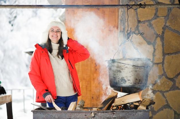 冬の屋外で夕食を調理する美しい女性。