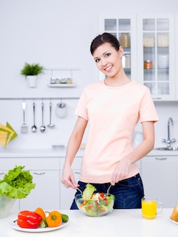 Красивая женщина готовит здоровую пищу на кухне