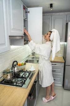 モダンなキッチンで料理をする美しい女性。健康食品。ダイエットコンセプト