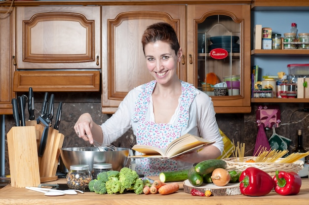 Beautiful woman cooking vegetables with cookbook