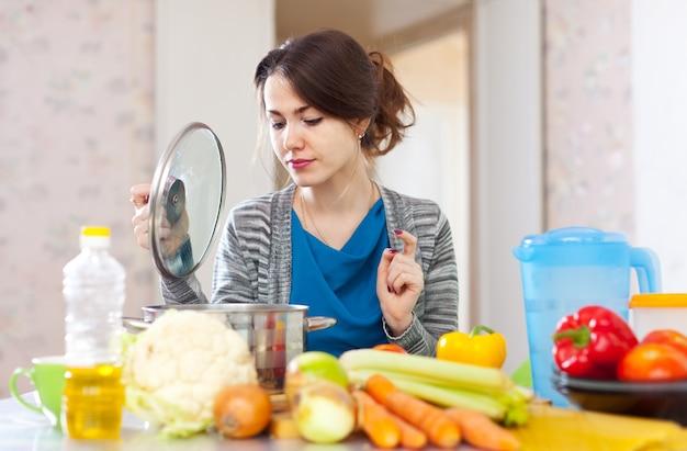 Beautiful woman cooking vegetarian lunch