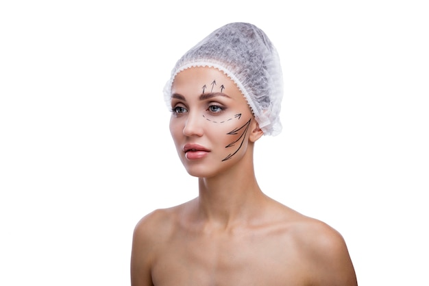 Beautiful woman cosmetology beauty face medical disposable cap markings on the face