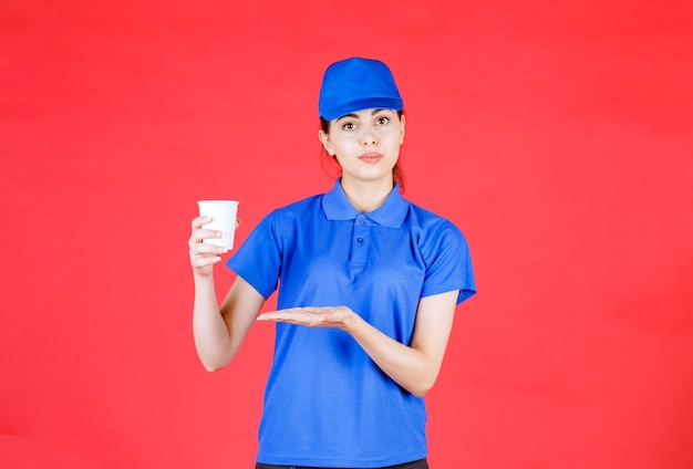 Beautiful woman courier in blue outfit holding cup of tea on red.