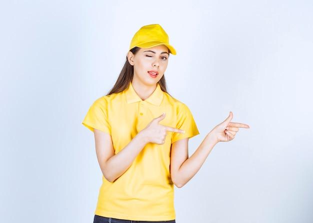 白い壁の上に立ってポーズをとって黄色の制服を着た美しい女性の宅配便。
