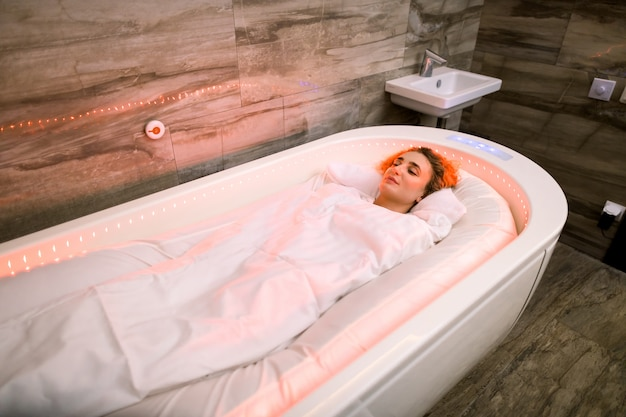 스파 침대에 누워 특별한 뜨거운 담요로 덮여 아름다운 여자, 뜨거운 스파 치료를 갖는