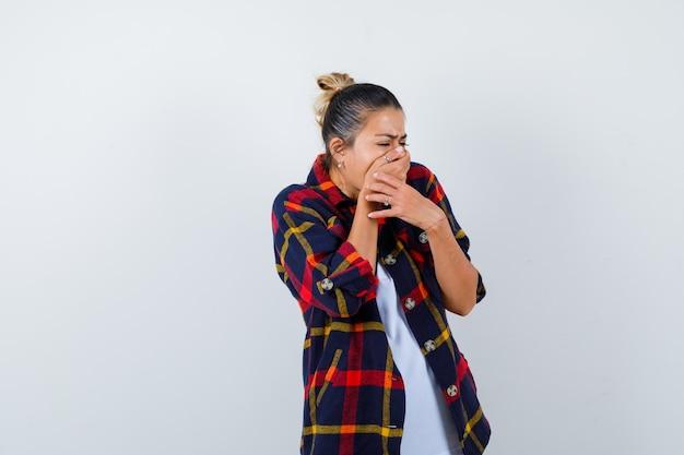 Bella donna che copre la bocca con le mani in maglietta bianca, camicia a quadretti e sembra scioccata, vista frontale.