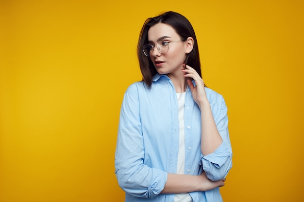 Beautiful woman crosses arm over waist, looks left side, wears casual clothes over yellow wall