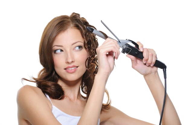 Beautiful woman curling her brunette hair with roller isolated on white
