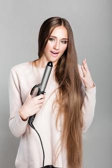 Красивая женщина, завивая длинные волосы с помощью щипцов для завивки. девушка обожгла палец