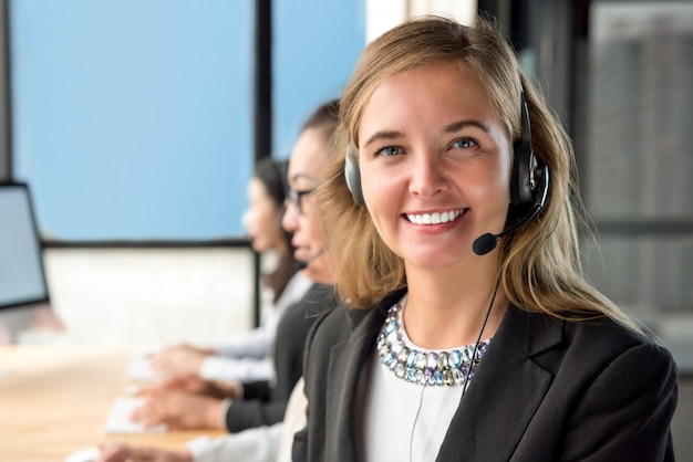 Beautiful woman customer service agent working in call center with her team