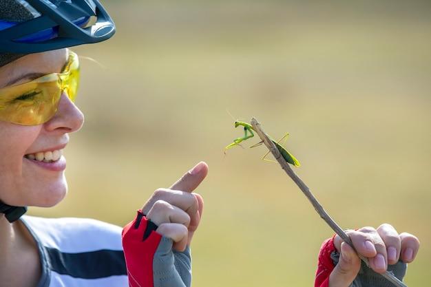 Велосипедист красивая женщина держит жука-богомола. природа и человек