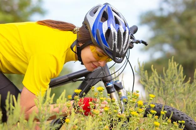 꽃 스니핑 노란색 필드에서 아름 다운 여자 사이클. 스포츠 및 레크리에이션. 자연과 사람