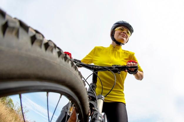 맑은 하늘 배경에 자전거에 노란색으로 아름 다운 여자 사이클. 스포츠 및 레크리에이션. 자연과 사람