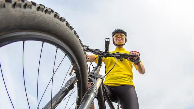 맑은 하늘 배경에 자전거에 노란색으로 아름 다운 여자 사이클
