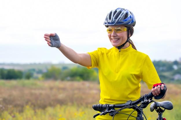 노란색에서 아름 다운 여자 사이클 그녀의 손을 앞으로 포인트