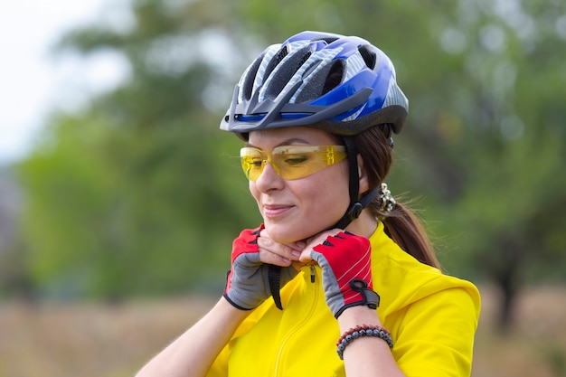 헬멧을 쓰고 노란색에서 아름 다운 여자 사이클입니다. 스포츠 및 레크리에이션.