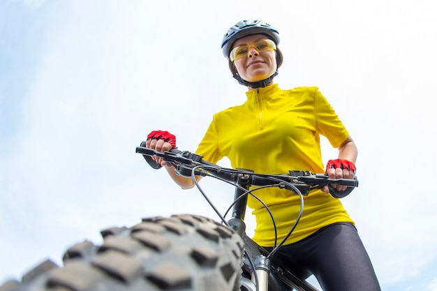 자전거의 바퀴를 기대하는 아름 다운 여자 사이클