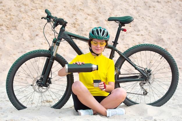아름 다운 여자 사이클 선수는 보온병에서 차를 부 어