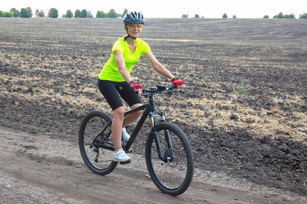 아름 다운 여자 사이클 필드에 자전거를 타고