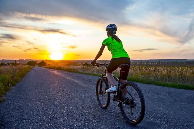 아름다운 여자 사이클 선수는 일몰 도로에서 자전거를 타고
