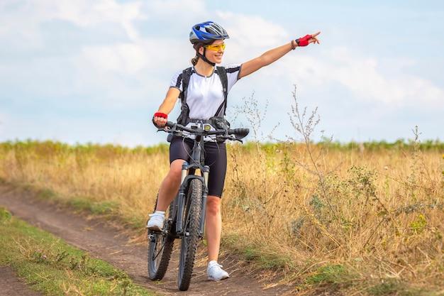 아름 다운 여자 사이클 자전거에 필드에 타기. 건강한 라이프 스타일과 스포츠. 여가와 취미