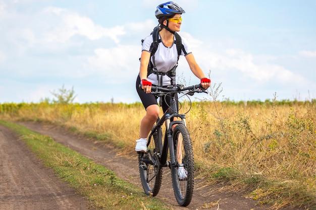 아름다운 여자 사이클 선수가 자전거를 타고 필드에 타기 =