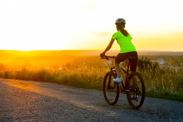 Велосипедист красивая женщина, езда на велосипеде по дороге к закату. природа и отдых. хобби и спорт