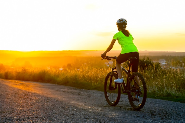 Beautiful woman cyclist riding a bike on the road towards the sunset. nature and recreation. hobbies and sports