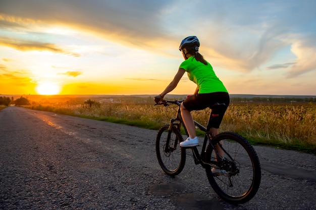 Beautiful woman cyclist riding a bike on the road towards the sunset.