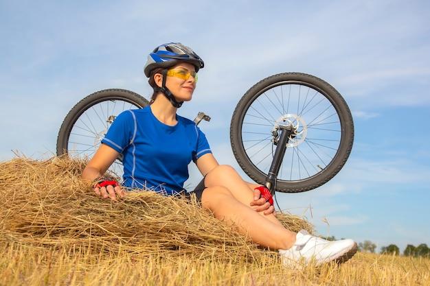 自転車の背景に乾いた草の上に座っている美しい女性サイクリスト。自然と人間