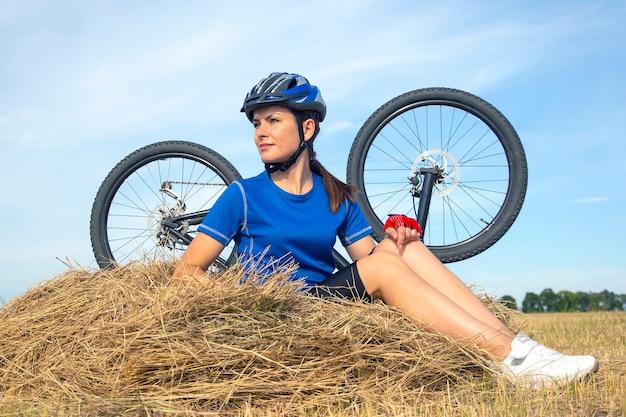 자전거의 표면에 마른 잔디에 앉아 아름 다운 여자 사이클. 자연과 사람