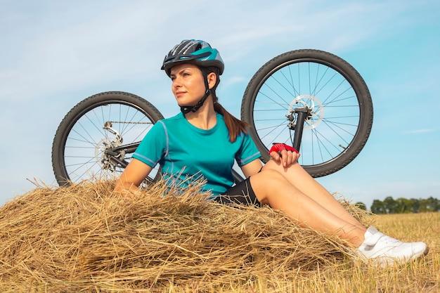 마른 잔디에 앉아 아름 다운 여자 사이클