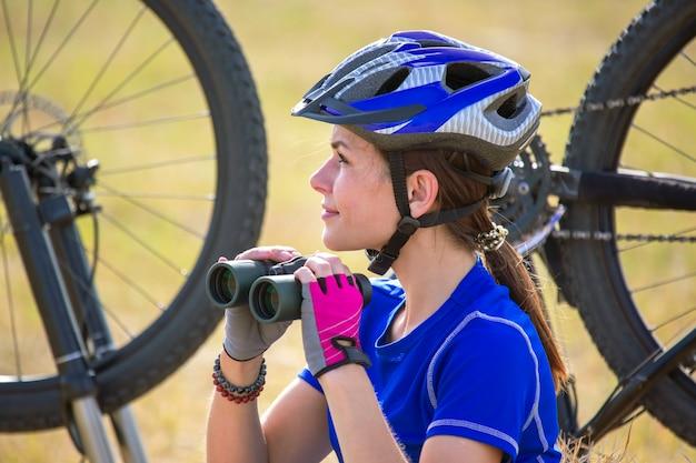 자전거의 배경에 손에 쌍안경으로 아름 다운 여자 사이클.