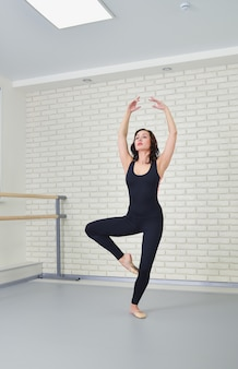 Beautiful woman dancer in black bodysuit gracefully dancing ballet at studio