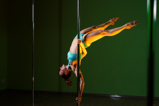 Beautiful woman dances near a pole on a colored background.